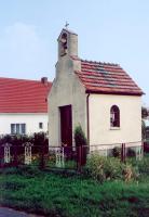 Murowana kapliczka z ceglanym dachem, w tle budynek
