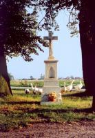 Murowany krzyż na postumencie pośród drzew