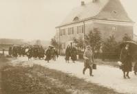 Widok na ulicę i idących po niej ludziach na tle budynku, zdjęcie archiwalne w sepii