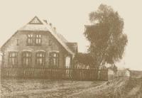 Stare sepiowe zdjęcie szkoły, budynek po lewej stronie zdjęcia, po prawej wysokie drzewo, przed zabudowaniami drewniany płot