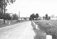 Stara czarnobiała fotografia ukazująca ulicę w perspektywie centralnej