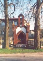 Murowana kapliczka ceglana, obok drzewa, w tle budynek mieszkalny