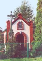 Biała kapliczka z czerwonymi zdobieniami, z przodku krzyż na postumencie