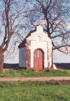 Biała kapliczka otoczona drzewami