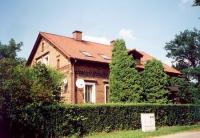 Ceglany budynek z żywopłotem i drzewami