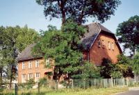 Ceglany budynek dawnej szkoły w Nędzy z dachem naczółkowym w otoczeniu drzew